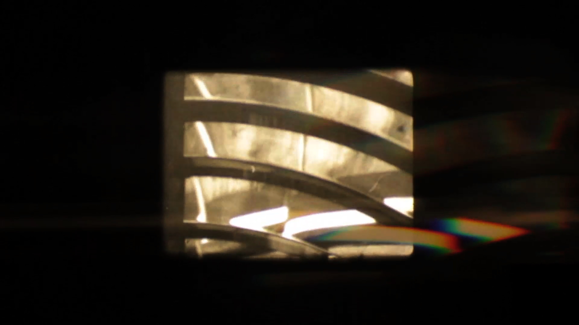 still image: close-up of the prism/bulb mechanism in a light house, refracted light creates a rainbow in bottom right corner